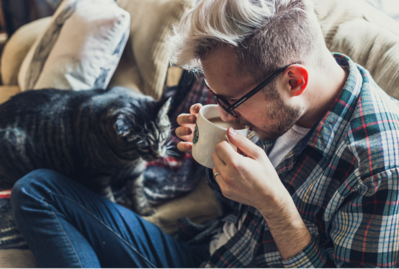 Man drinking tea and cuddling cat