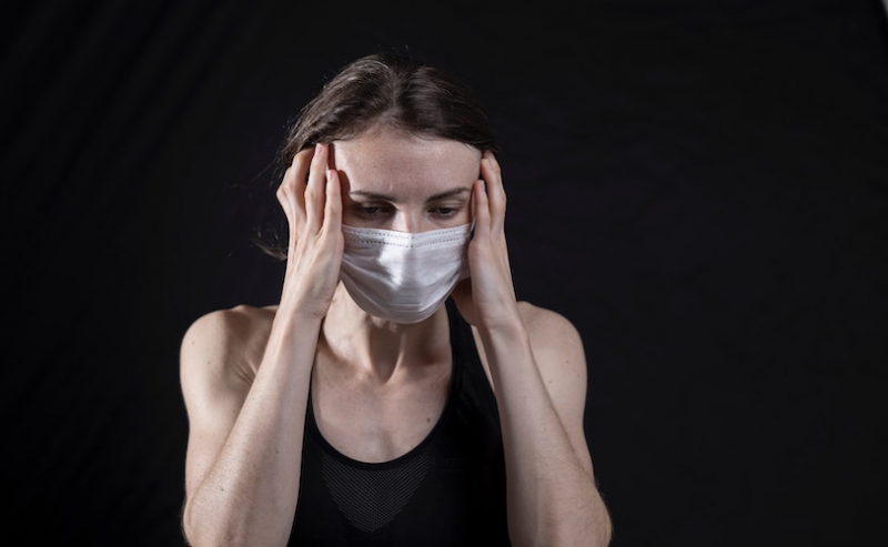 Woman wearing face mask with hands on head