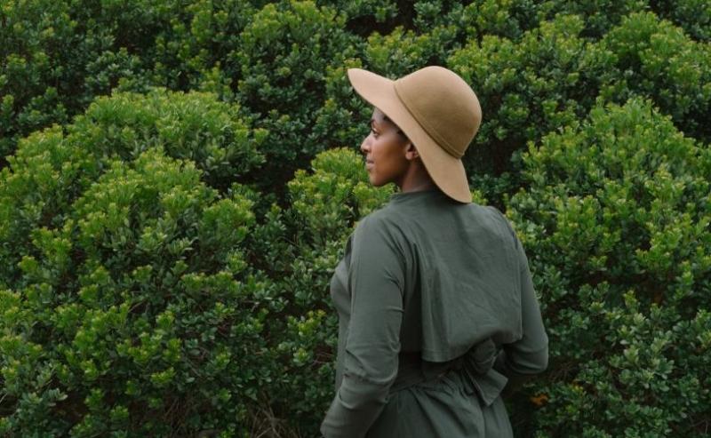 Woman standing by green bush