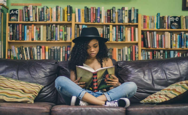 Girl sitting on sofa with book