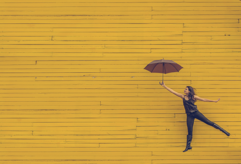 Woman leaping with umbrella on yellow background