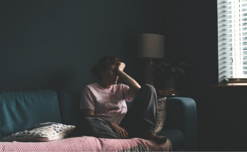 Woman sitting on sofa with head in hands