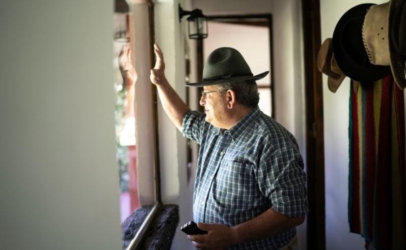 Man waving through window