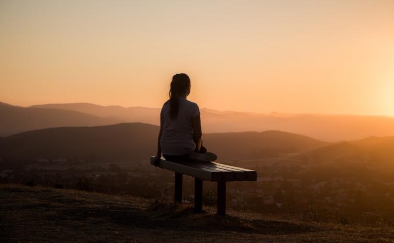Woman sitting on bench at sunrise