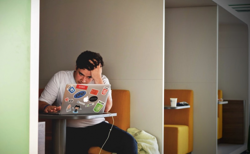 Man on laptop with head in hands