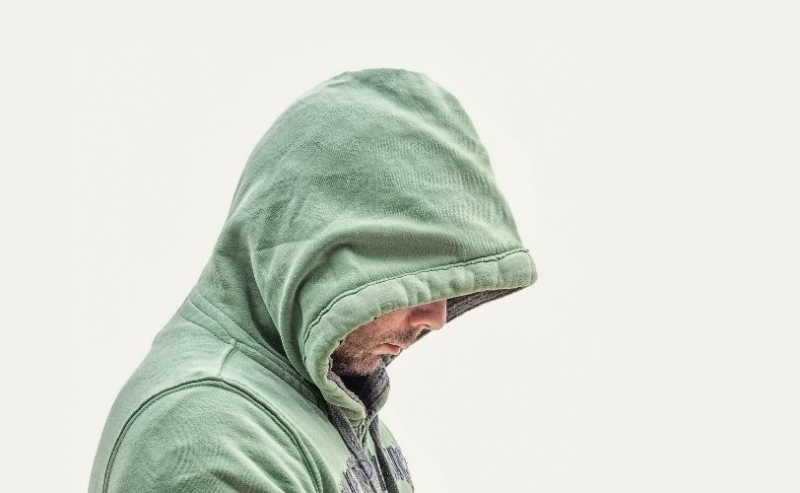 Man in hood with head lowered