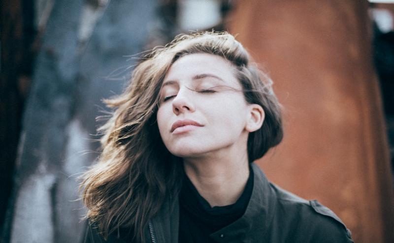 Woman facing sun with eyes shut