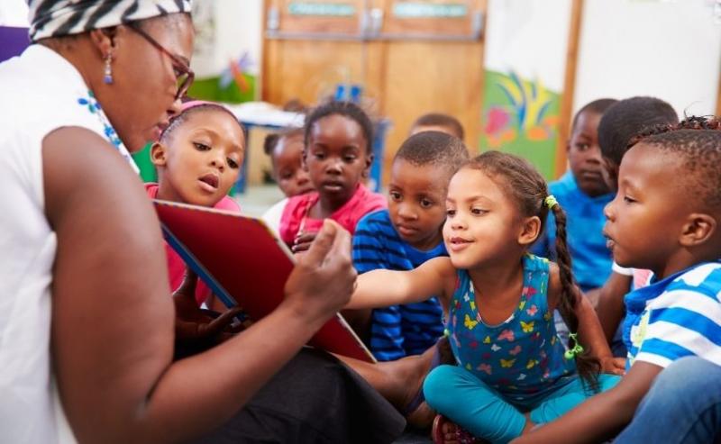A teacher showing children a book