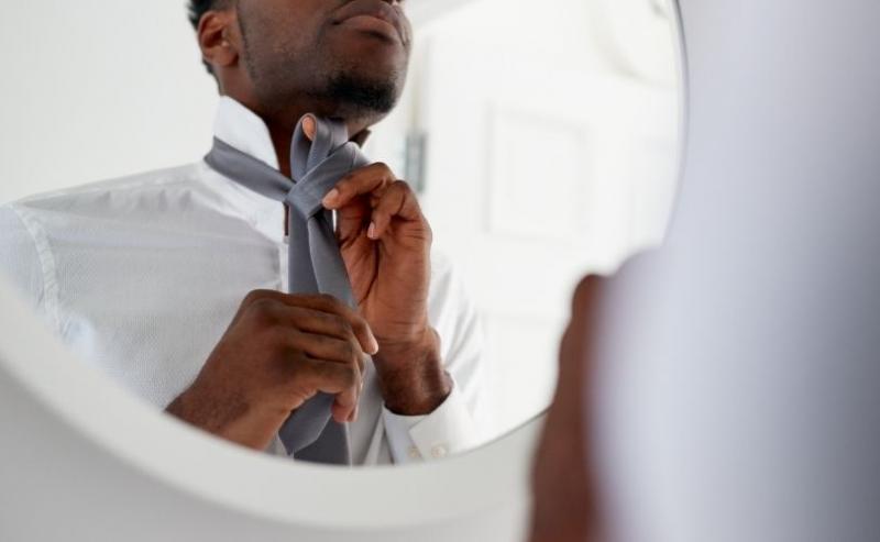 Man tying tie in mirror