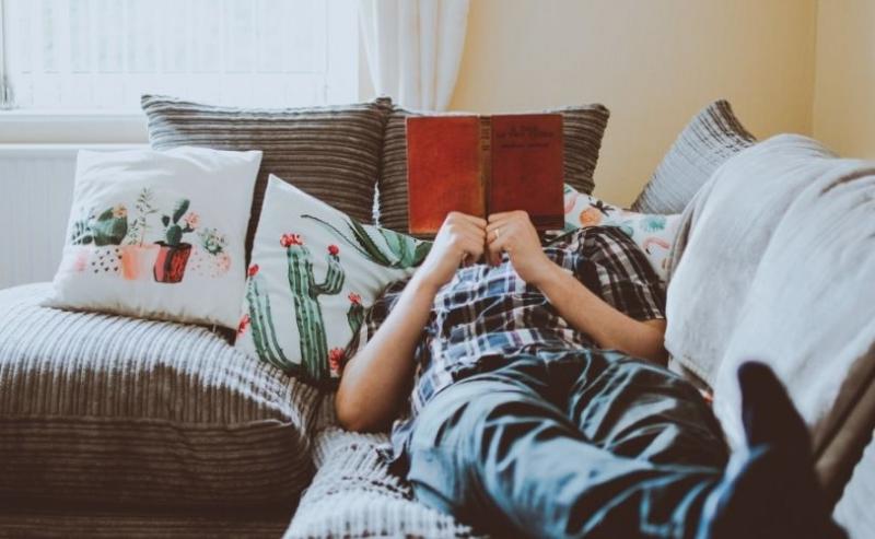 Man lying on sofa reading book