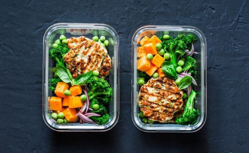 Two lunchboxes full with chicken and avocado