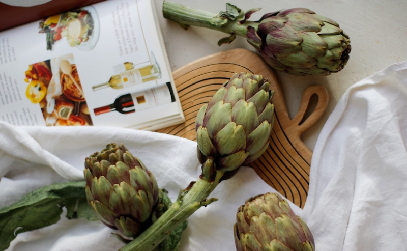 Artichokes on table with cookbook