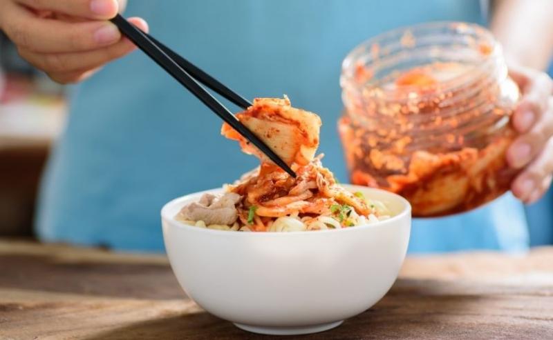 把kimchi放在碗的妇女