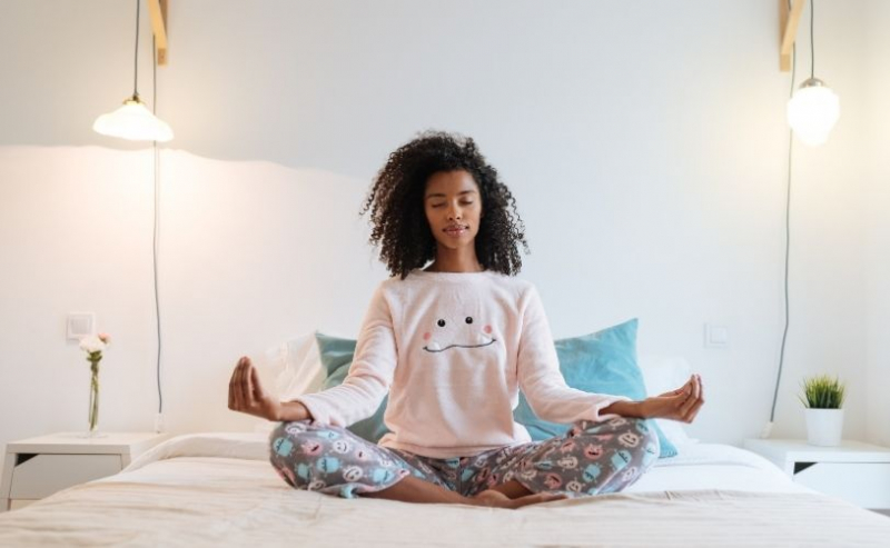 Woman meditating on bed