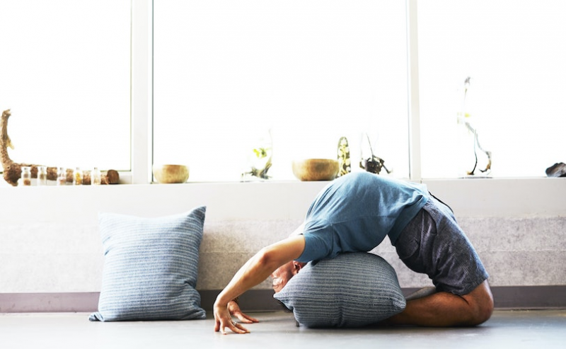 Man doing yoga pose with cushions