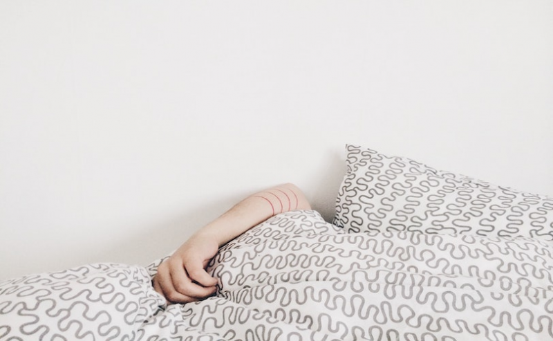 Woman asleep with duvet covering face